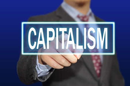 capitalism: Business concept image of a businessman clicking Capitalism button on virtual screen over blue background