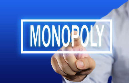 monopoly money: Business concept image of a businessman clicking Monopoly button on virtual screen over blue background Stock Photo