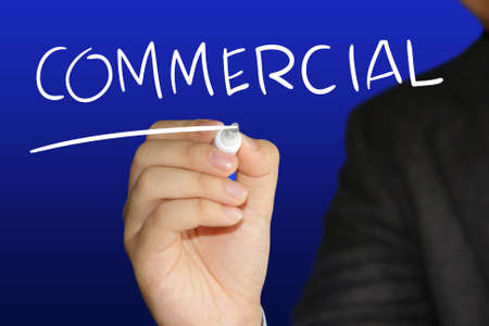 Business concept image of a businessman holding marker and write Commercial over blue background photo