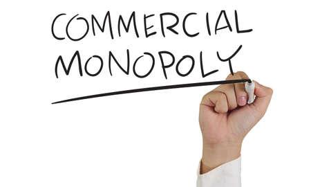 monopoly: Imagen Concepto de negocio de un marcador de explotación de la mano y escribir Monopolio Comercial aislado en blanco Foto de archivo