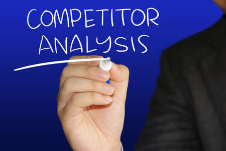 strategic advantage: Business concept image of a businessman holding marker and write Competitor Analysis over blue background Stock Photo