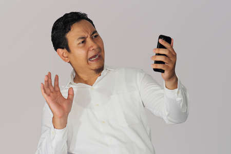 freaked: Shocked Asian businessman with scared gesture after receiving news from his cell phone