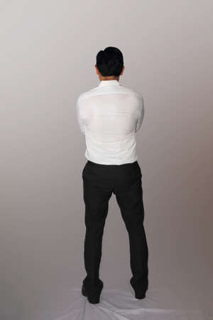 hands behind back: Rear view of a businessman thinking and looking forward