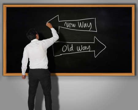 new way: Businessman writing New Way Old Way words and arrows with chalk on a blackboard in front of him Stock Photo