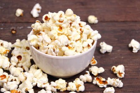 bowl of popcorn: Food photography closeup photo of popcorn in white bowl on wooden table
