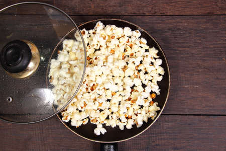 eating popcorn: Food photography closeup photo of popcorn in a pan on wooden table
