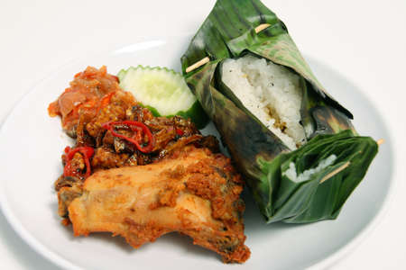 Asian food Baked Rice in banana leaf with crunchy fried chicken and hot chili sauce Banco de Imagens
