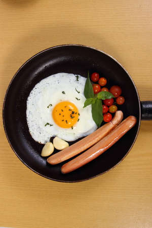 food photography: Food photography closeup photo of bullseye egg and sausage in a pan on wooden table