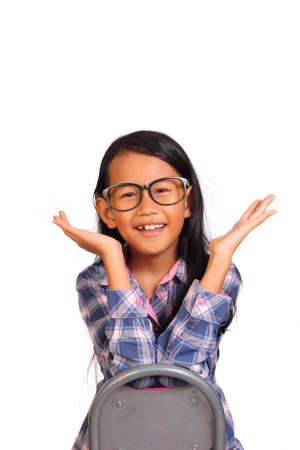backward: Cute little girl with glasses sitting backward on chair smiling and showing hurray gesture isolated on white