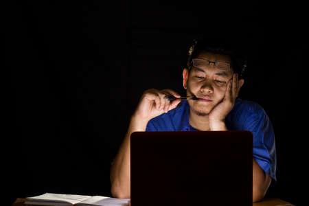 若い男が暗闇の中で彼のラップトップの前で一心に考えること