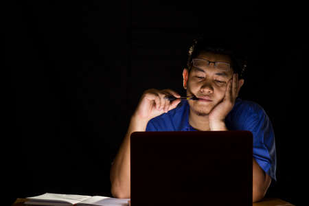 Young man thinking hard in front of his laptop in the dark