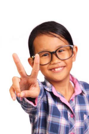 niños sonriendo: Niña linda con gafas muestran dos dedos o gesto de paz delante de ella aislados en blanco