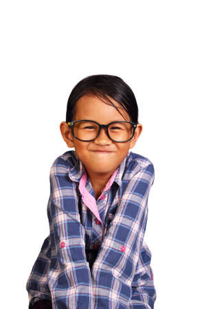 tight: Cute Little girl with glasses performing tight lipped smile while closing her shoulders isolated on white