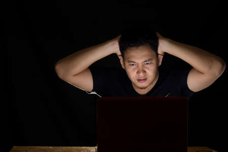 upset: Young man shocked in front of his laptop in the dark