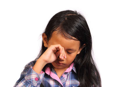 indonesia girl: Sad and crying little girl looking down isolated on white Stock Photo