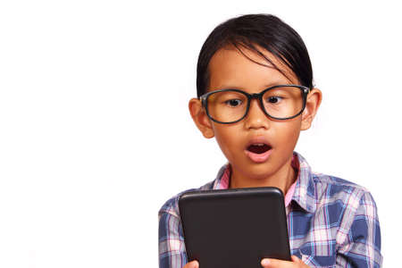 habbit: Little girl with glasses shocked while looking her tablet isolated on white