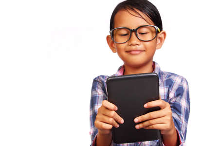 habbit: Little girl with glasses smiling while looking her tablet isolated on white Stock Photo