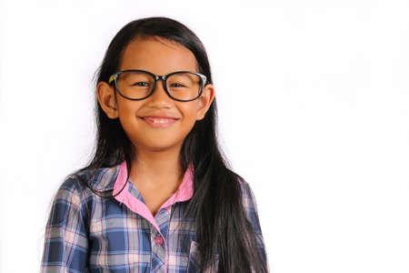 niños sonriendo: Niña asiática feliz con los vidrios de pie y sonriente aislados sobre blanco