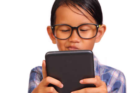 kids playing video games: Little girl with glasses seriously playing her tablet isolated on white Stock Photo