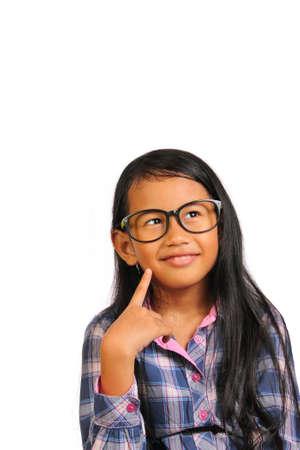 niña pensando: Niña con gafas pensando y sonriente mirando hacia arriba a la parte superior, mientras que tocando su mejilla aislado en blanco