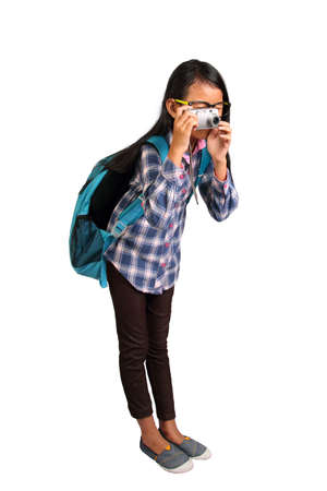 camera girl: Little girl with glasses and backpack standing and taking photo with her camera isolated on white