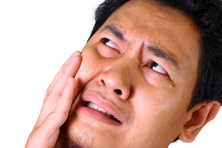 cheek to cheek: Young Asian man in pain of toothache holding his cheek Stock Photo