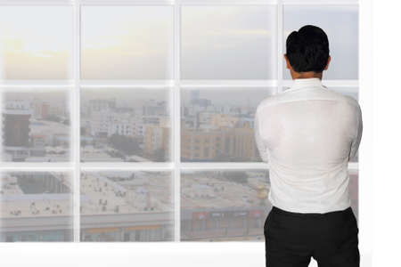 window view: Vision concept image rear view of a businessman starring outside window looking at opportunities Stock Photo