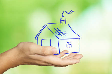 hand holding house: Image of a hand holding house doodle image over green blur background