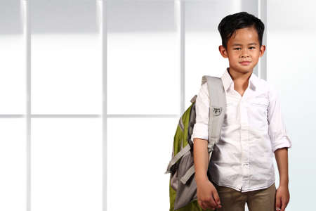 asian boy: Young Asian boy student standing and smiling over bright background Stock Photo