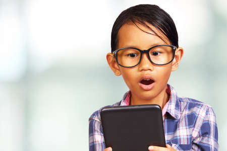 kids playing video games: Young Asian girl shocked looking at her tablet over bright background