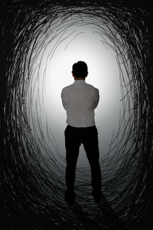 starring: Challenge concept image rear view of a businessman starring at bright light at the end of dark tunnel