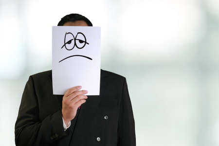 the mask: Business concept image of a businessman holding white paper mask with sad and tired face drawn on it