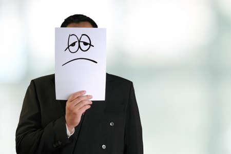antifaz: empresas concepto de imagen de un hombre de negocios la celebraci�n de la m�scara de papel blanco con cara triste y cansado dibujado en �l