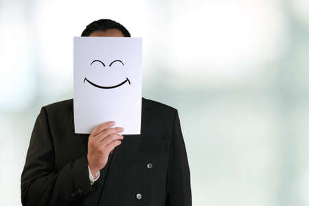 masks: Business concept image of a businessman holding white paper mask with happy smiling face drawn on it Stock Photo