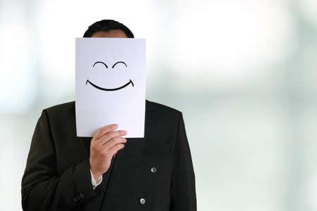 sonrisa: empresas concepto de imagen de un hombre de negocios la celebración de la máscara de papel blanco con cara sonriente feliz dibujada en él