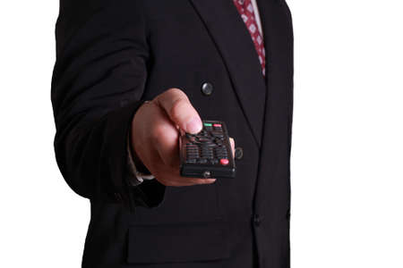 black business men: Business concept image of a businessman holding and clicking remote control, front view isolated on white