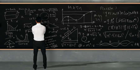 equivalents: Businessman thinking and standing facing on large blackboard with math equivalents written on it Stock Photo