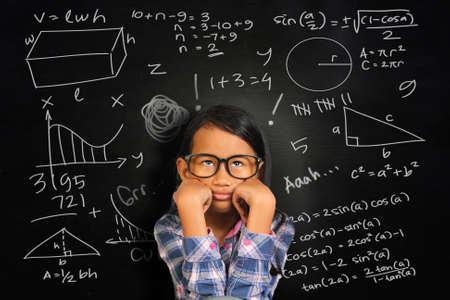 niños enfermos: Asia chica estudiante pequeño con los vidrios que muestra aburrido y cansado en la pizarra verde con los equivalentes de matemáticas escritas en él