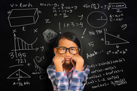 kids learning: Little Asian student girl with glasses showing bored and tired over green chalkboard with math equivalents written on it
