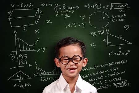 matemáticas: El pequeño niño genio estudiante asiático con gafas sonriendo en la pizarra verde con los equivalentes de matemáticas escrito en él