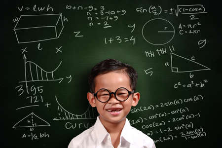 glass background: Little genius Asian student boy with glasses smiling over green chalkboard with math equivalents written on it