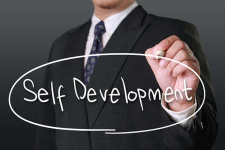 self development: Motivational business concept, image of a businessman holding marker and write Self Development words