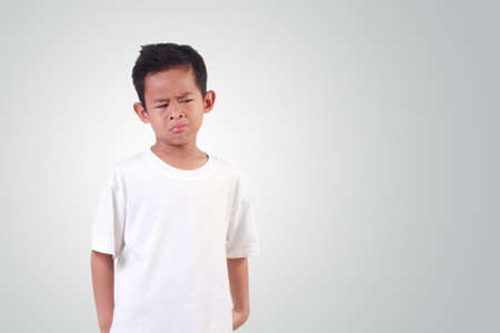 Portrait of Sad Asian boy with black hair wearing white shirt crying