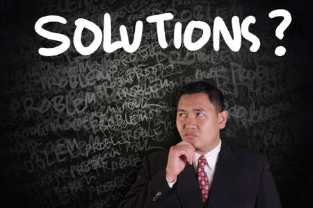 problems solutions: Problems and Solutions Concept, Asian businessman thinking of solutions with problems words on chalk board around him