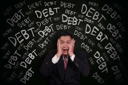 Stress concept, Asian businessman shocked and scream under pressure with debt words on chalk board around him