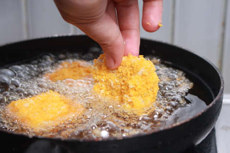 deep fry: Close up image of chef hand putting chicken nuggets tempura in to hot oil pan for deep fry cooking