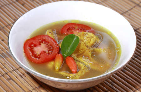 soup bowl: Food photography, Indonesian Makassar traditional food palumara ikan or fish soup served with chilli and tomatoe in white bowl Stock Photo