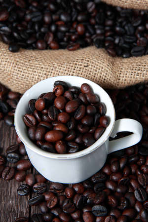 gunny: Dark roasted coffee beans in white cup with blurred coffee beans and gunny sack texture on background