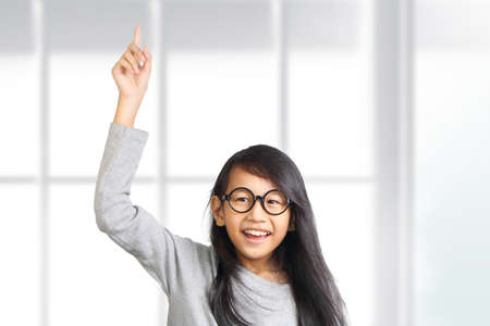 respond: Portrait of beautiful little Asian student girl smiling enthusiastic and raise her hand and pointing finger up to get attention from teacher in class