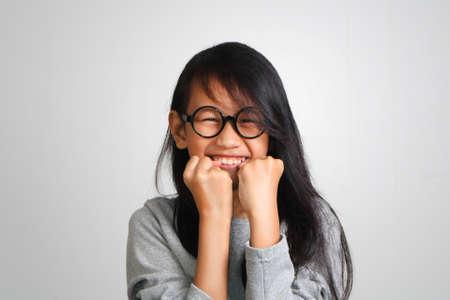 Portrait von sehr glücklich hübsch schöne asiatische Mädchen mit langen schwarzen Haaren trägt eine Brille begeistert zeigt Glück Geste zu gewinnen Standard-Bild
